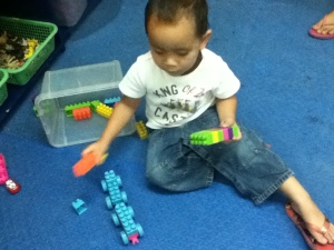 Eli makes a 'firetruck' from his wheeled Lego pieces!