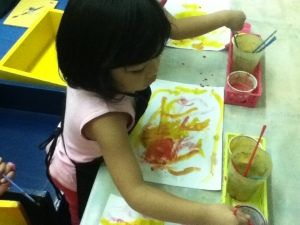 Lexi mixes red and yellow paint to make orange! Clever!