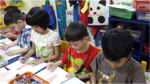 "Here is Agui, Macy, Monch, and Jonvi, working on the art activity, ""What Do I Do with My Family?"""